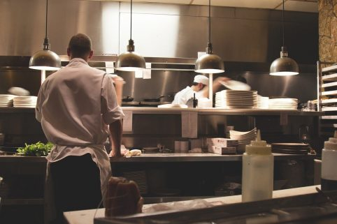 Photo of a chef working in a polished kitchen restaurant space.